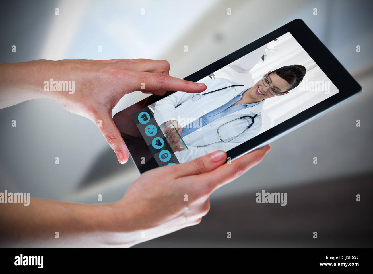 Hands using digital tablet against white background against bright white room with windows - Stock Photo