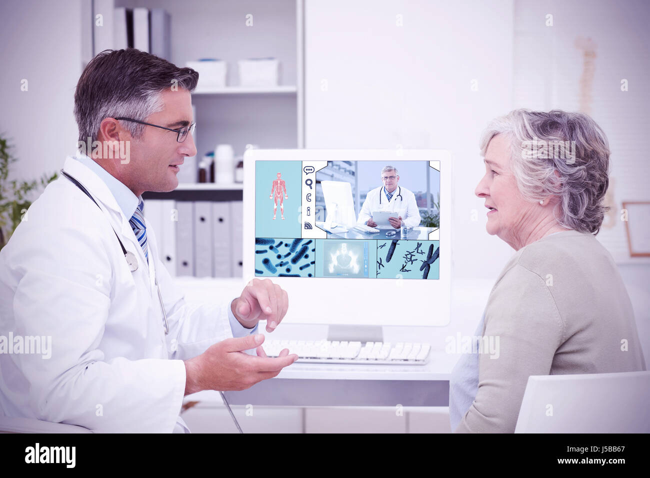 uniformed doctor against male doctor conversing with senior patient at table - Stock Image