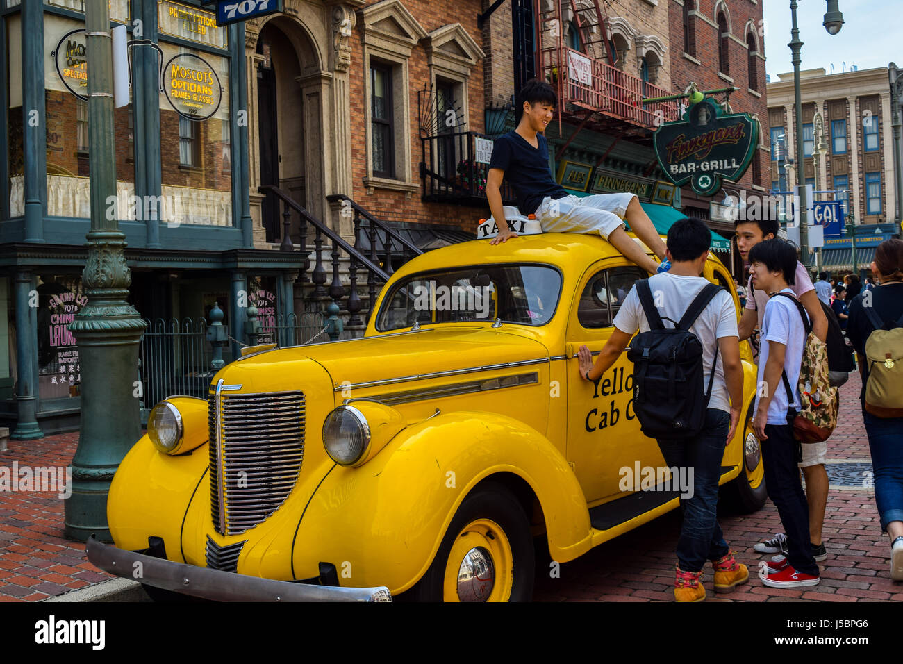 Young boys enjoying a fun Saturday, goofing and playing around a yellow cab with friends in Universal Studios Japan - Stock Image