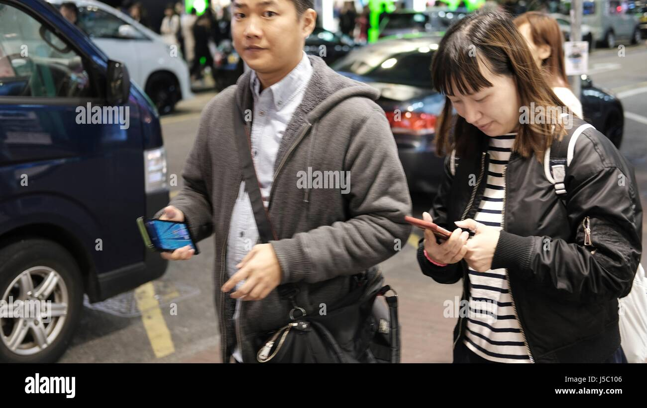 Pedestrian People in Public Using Mobile Cell Phones for Communication at Ladies Market in Mongkok Kowloon Hong - Stock Image