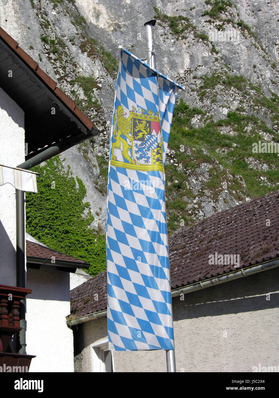 house building bavaria flag place mountain blue humans human beings people folk - Stock Image