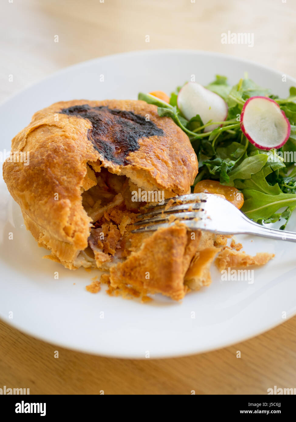 Chicken pot pie (chicken and mushroom pie) and arugula salad at District Café & Bakery in Edmonton, Alberta, - Stock Image