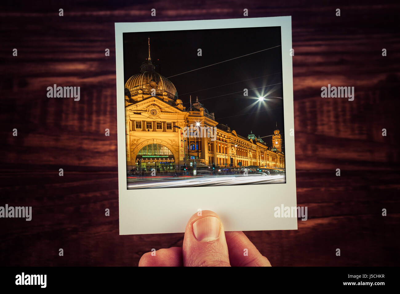 Hand holding polaroid postcard of Flinders Street Station at night. Melbourne, Australia. Travel memories scrapbooking - Stock Image