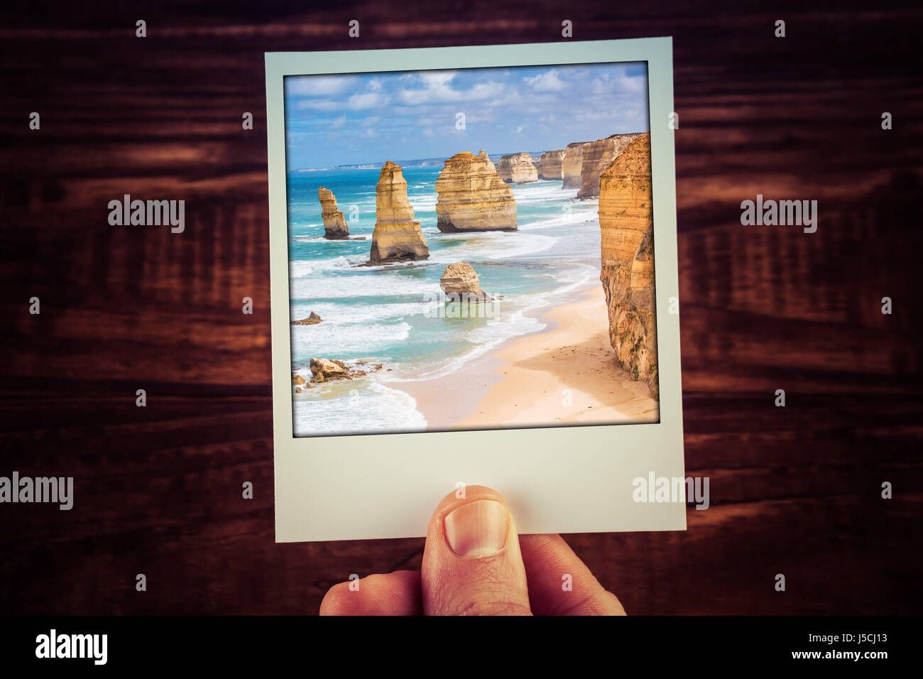 Hand holding polaroid photograph of The Twelve Apostles, Great Ocean Road, Australia with copy space. Travel memories - Stock Image