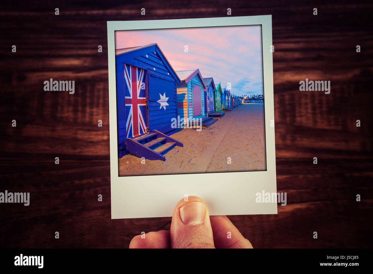 Hand holding polaroid photograph of famous Brighton Beach Boxes in Melbourne, Australia. Travel memories scrapbooking - Stock Image