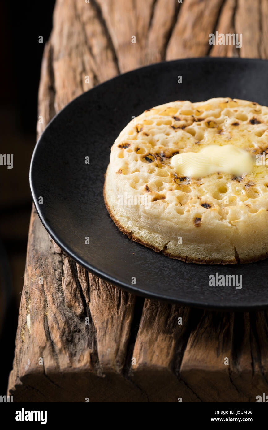 Toasted crumpets on a rustic wooden table. - Stock Image