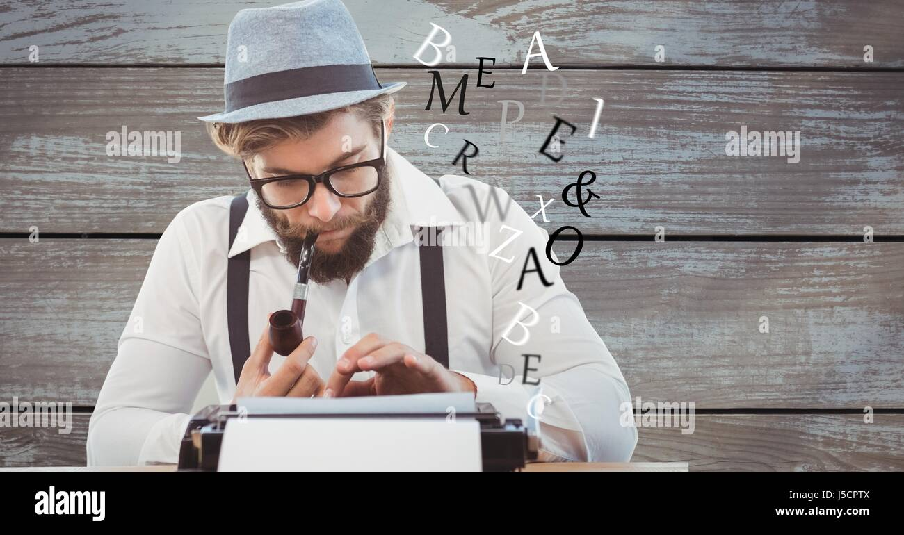 Digital composite of Hipster using typewriter while smoking pipe against wooden wall - Stock Image