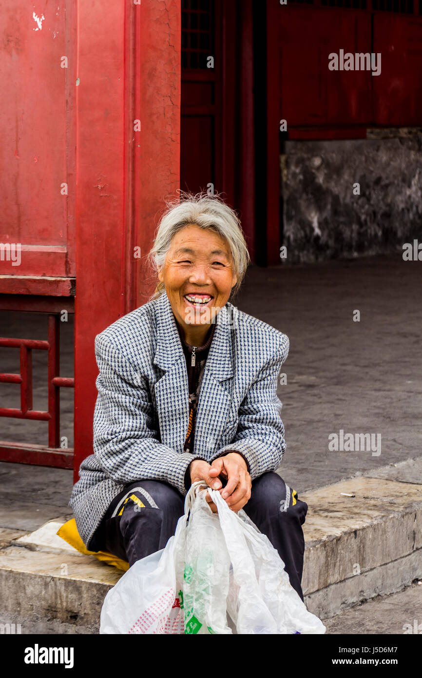 BEIJING, CHINA-26th MARCH 2014:-The old lady is resting beside a red wall outside the forbidden city Stock Photo