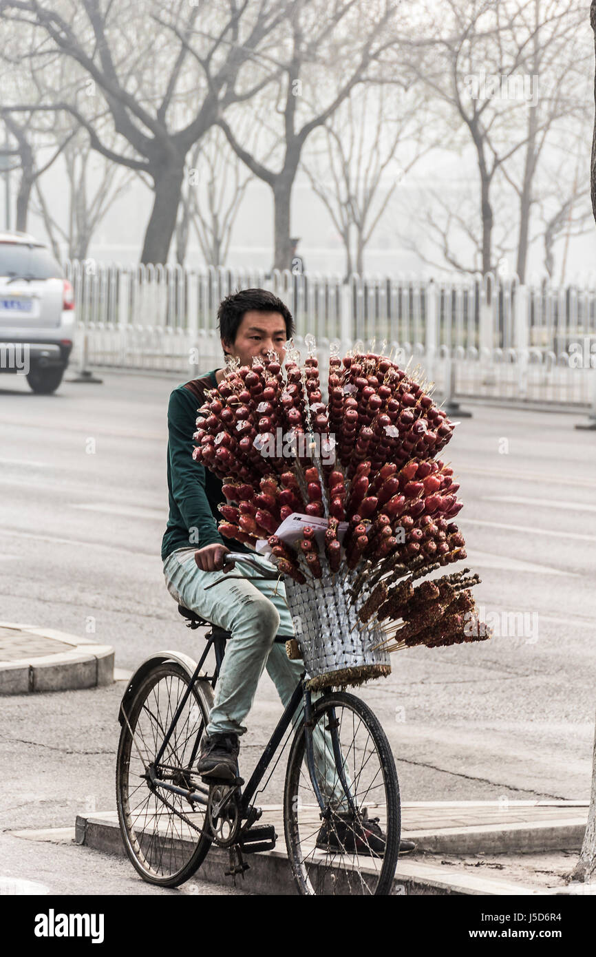 BEIJING, CHINA-26th MARCH 2014:-Street vendor with sugar coated syrup strawberries for sale Stock Photo