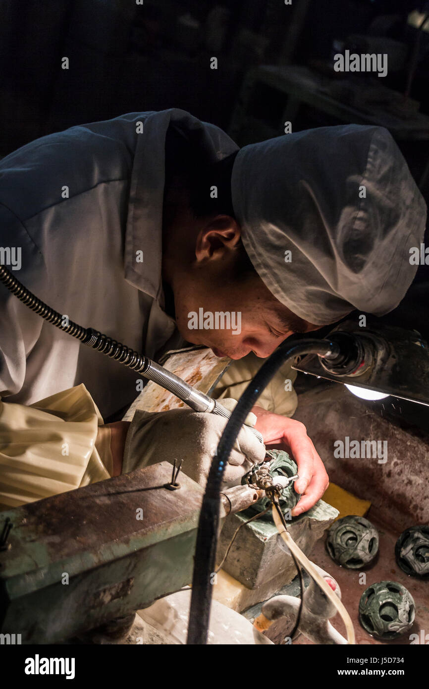 BEIJING, CHINA-26th MARCH 2014:- The carvers are cutting jade into intricate patterns for tourists. Stock Photo
