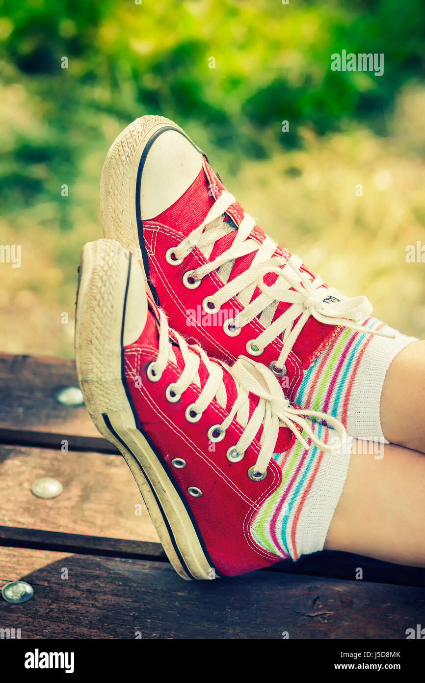 Woman's feet in a red canvas sneakers with colorful socks, sitting on a bench - Stock Image
