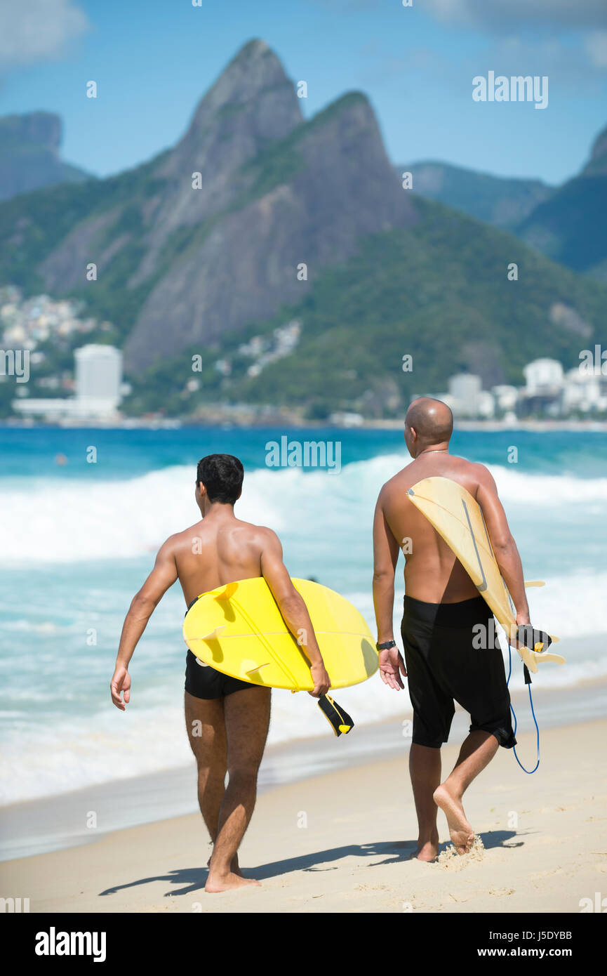 Young Brazilian surfers walking with their surfboards from Arpoador, the popular surf spot, toward Ipanema Beach, - Stock Image