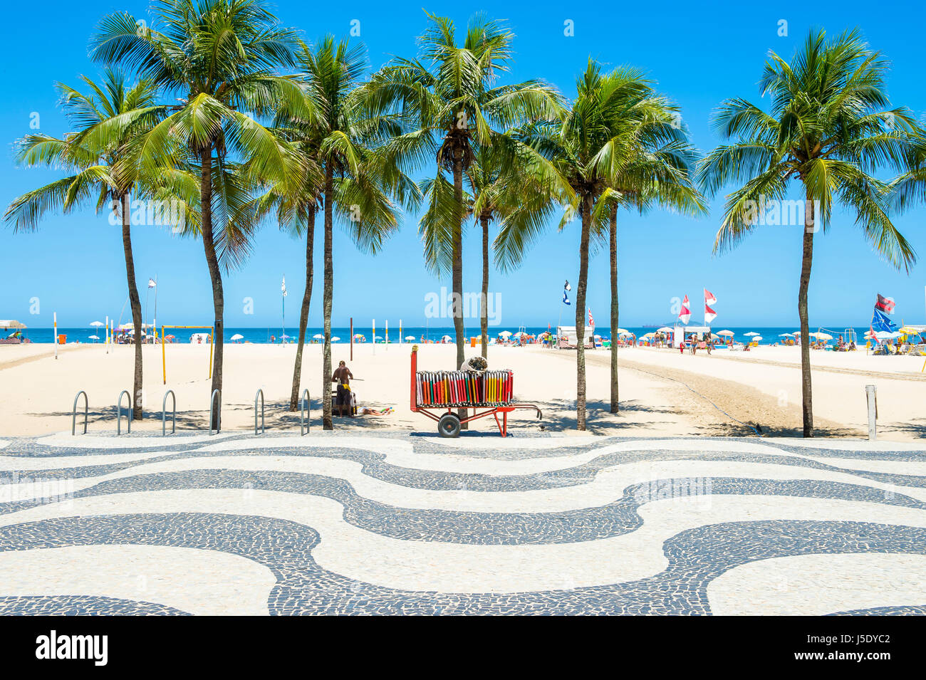 Bright scenic view of Copacabana Beach with palm trees beside the iconic boardwalk in Rio de Janeiro, Brazil - Stock Image