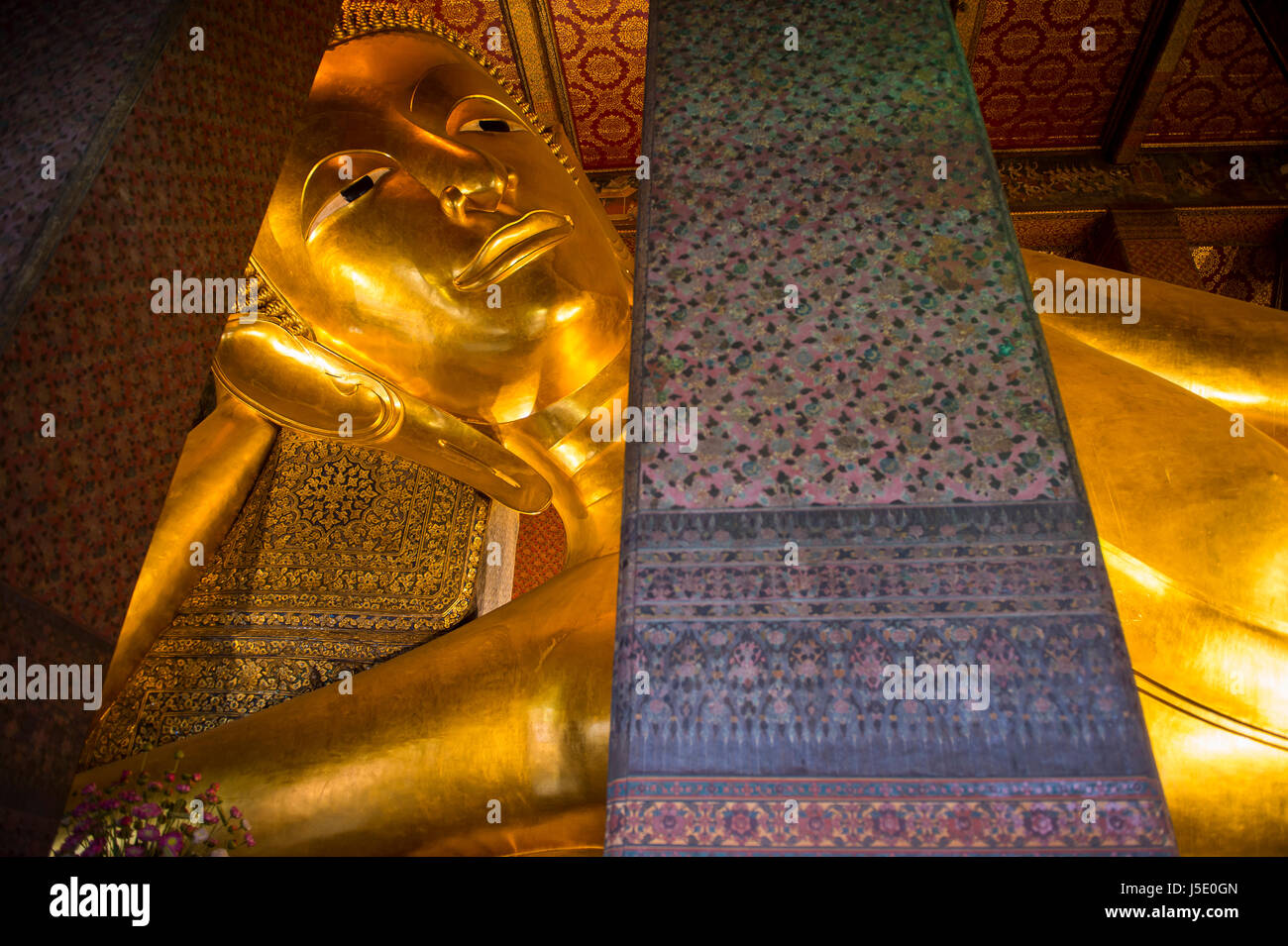 Close-up of the giant golden statue at the Temple of the Reclining Buddha in Bangkok, Thailand - Stock Image