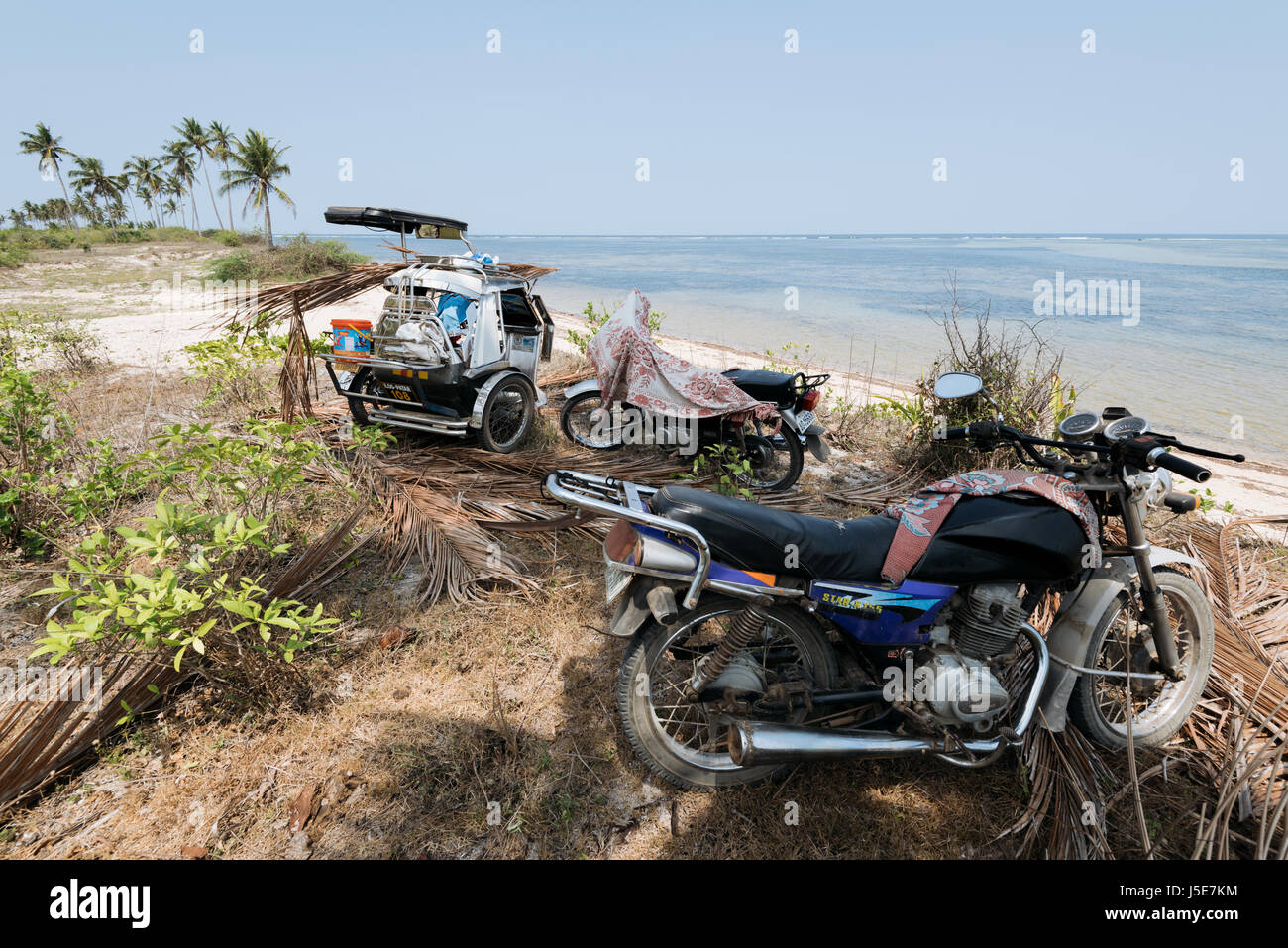 Quezon Island, Philippines - April 13, 2017: Tricycle and motorcycles left behind on a beach by fishermans who went - Stock Image