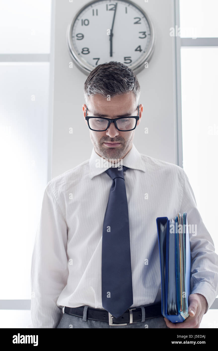 Frustrated businessman in the office standing under a clock, punctuality and time slave concept - Stock Image