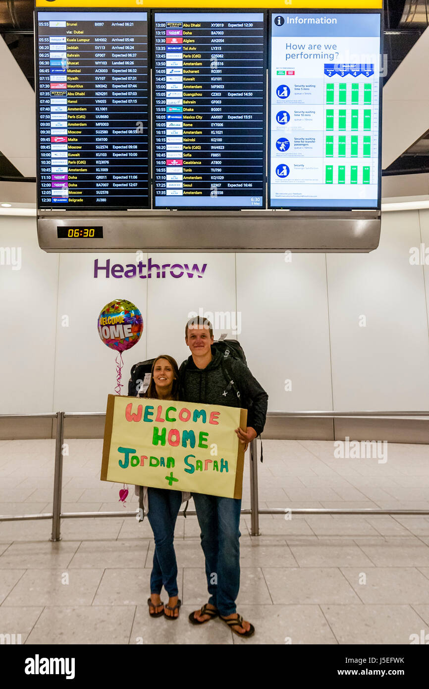 A Young Couple Holding Up A Welcome Home Sign After Returning Home From Travelling, Heathrow Airport, London, UK - Stock Image