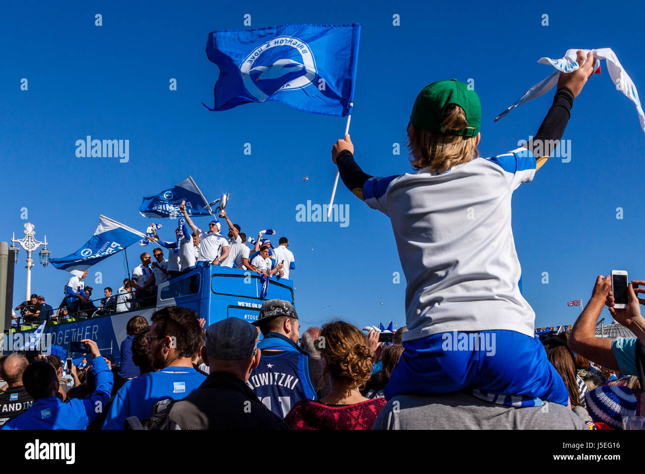A Cheering Young Brighton and Hove Albion Football Fan Watches As The Team Bus Passes During The Club's Promotion - Stock Image