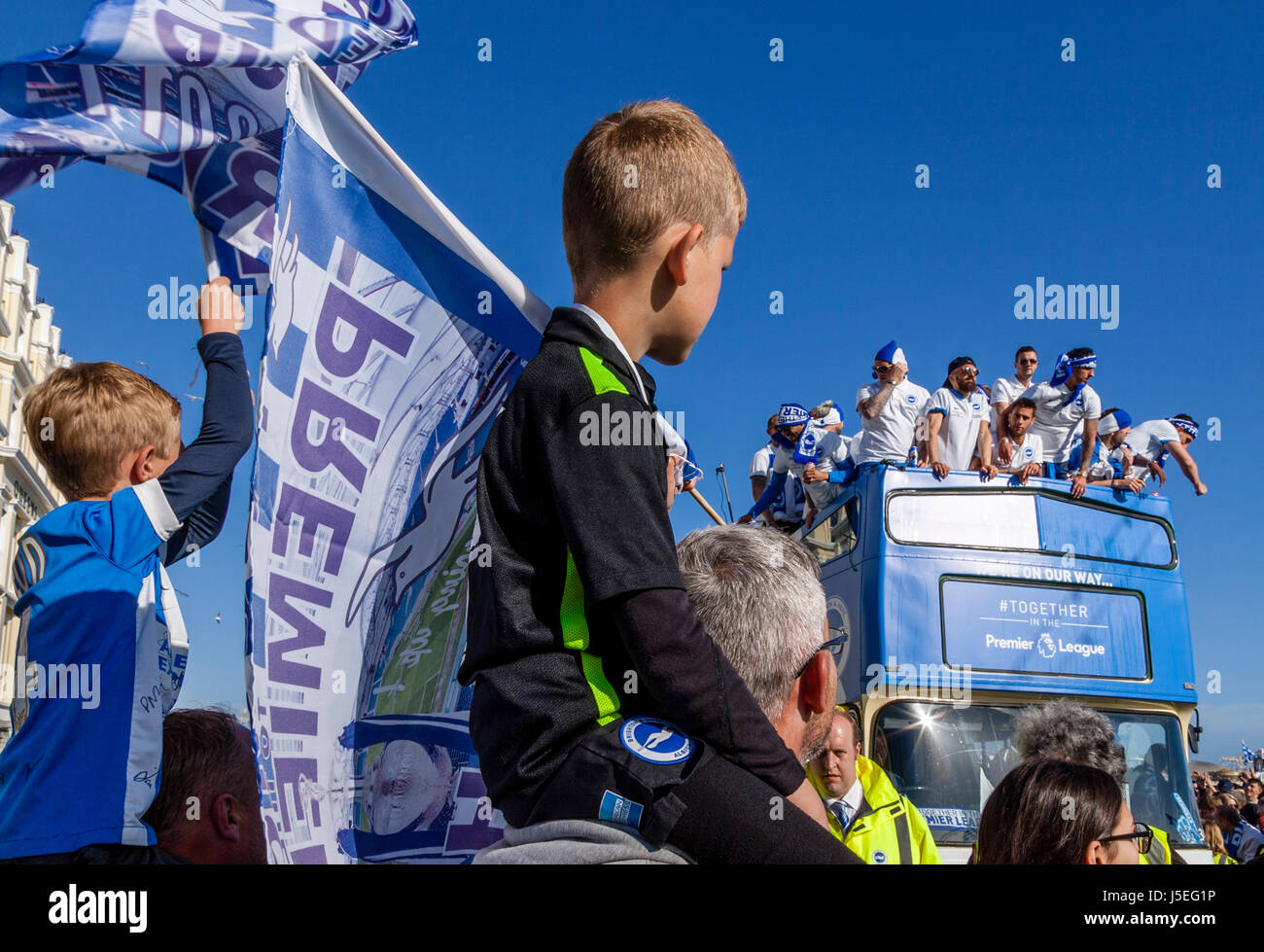 Young Brighton and Hove Albion Football Fans Watch As The Team Bus Passes During The Club's Promotion Parade, - Stock Image