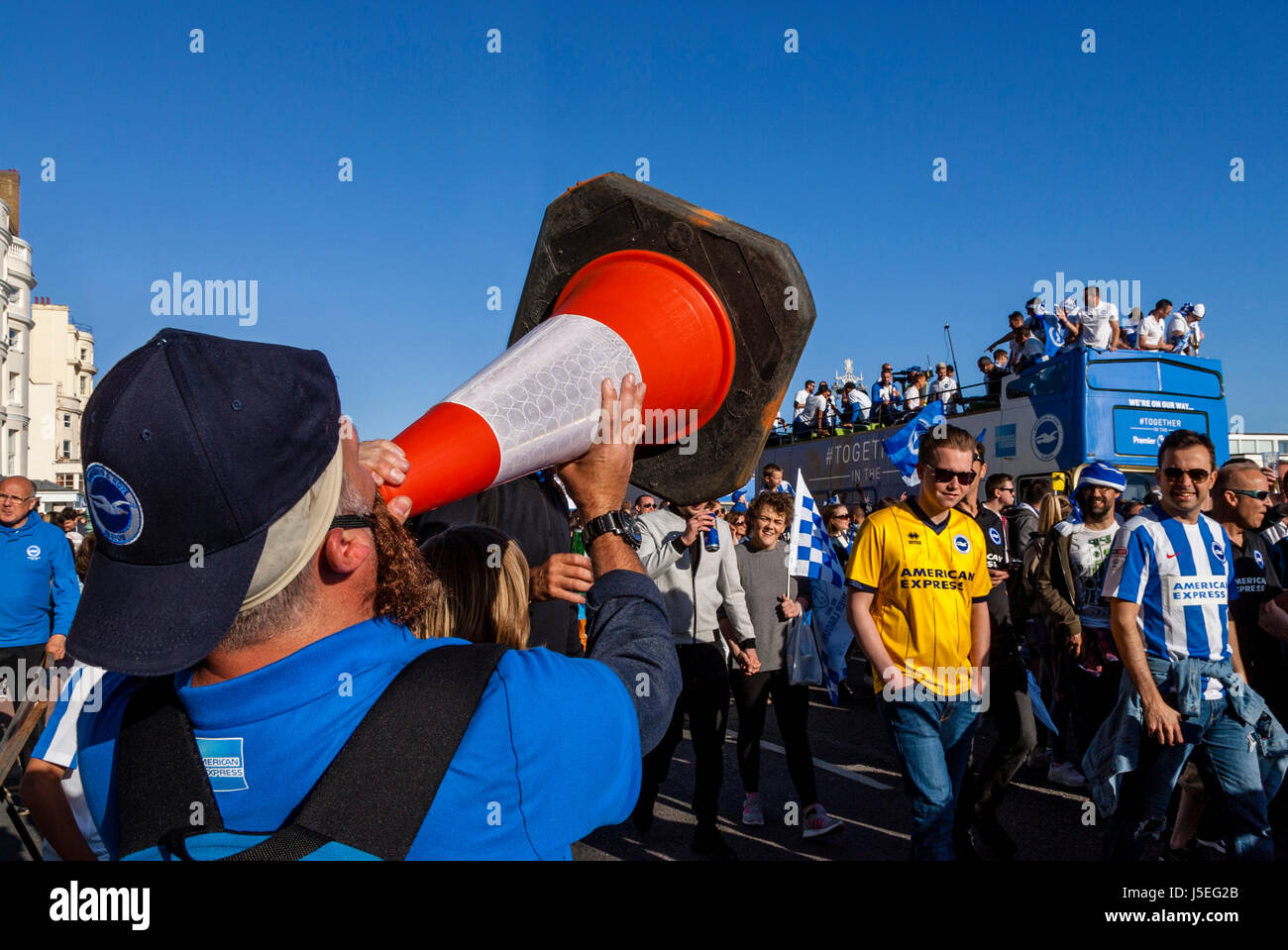 A Brighton and Hove Albion Football Fan Shouts Into A Traffic Cone As The The Team Bus Passes During The Club's - Stock Image