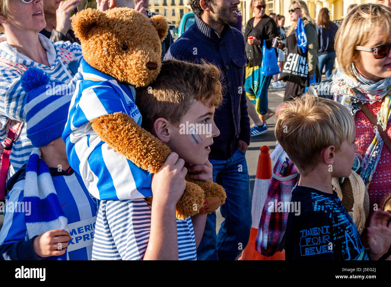 Young Brighton and Hove Albion Football Fans Watch The Team Bus Passing Along The Seafront During The Club's - Stock Image