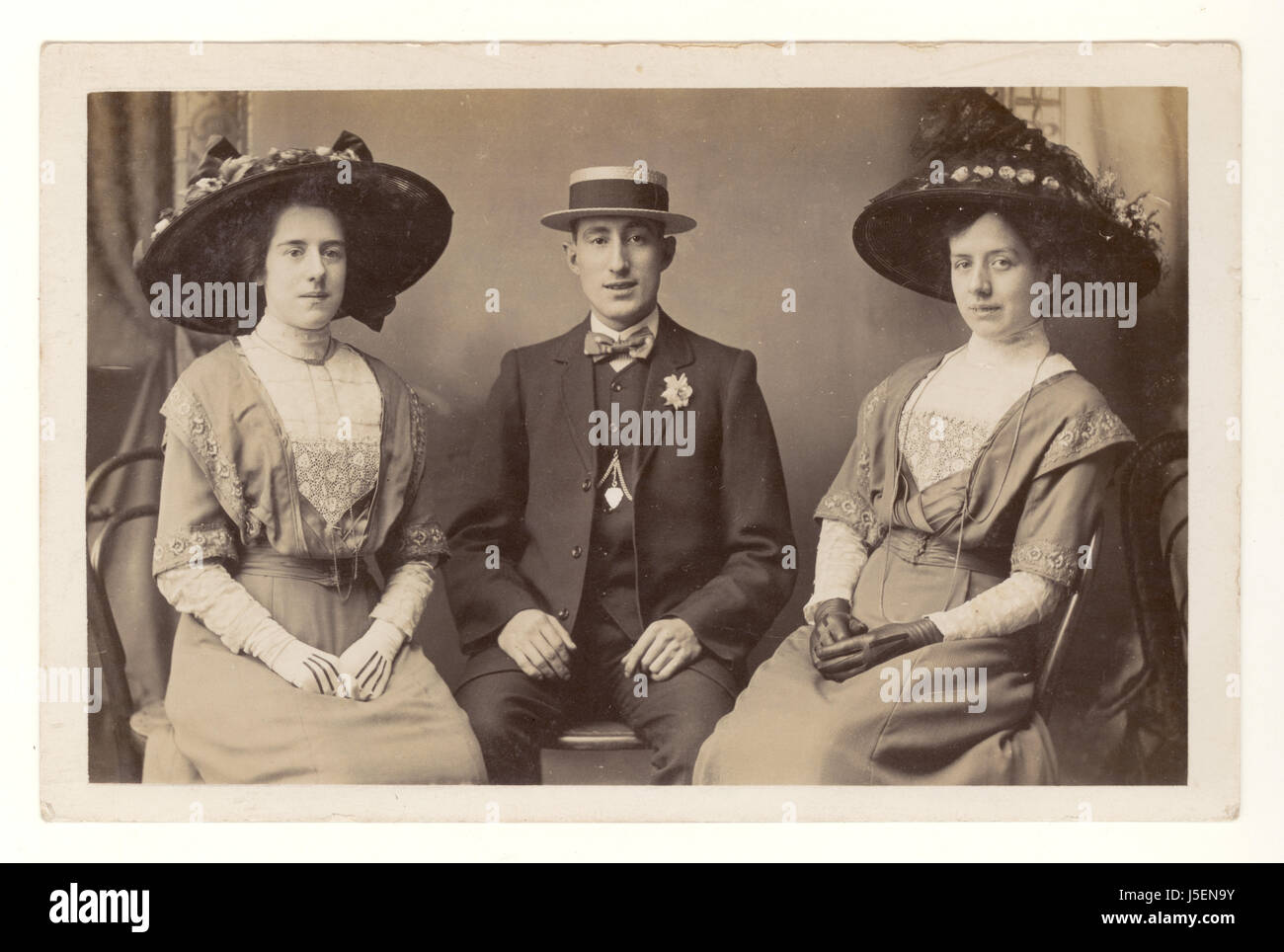 Edwardian postcard of smart women in large hats and young man in a straw boater hat posing for a studio portrait, - Stock Image