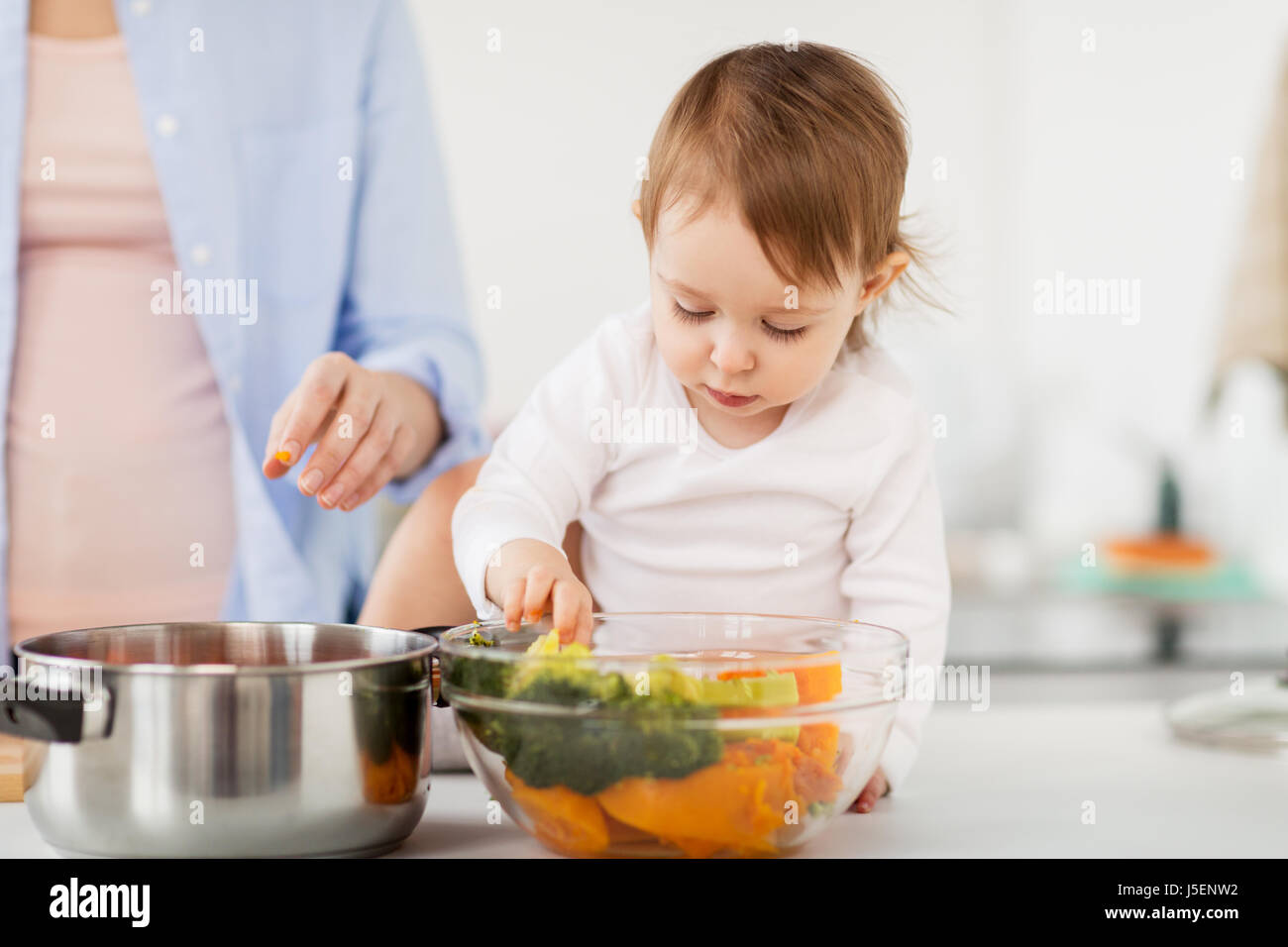 baby with vegetables and mother cooking at home - Stock Image