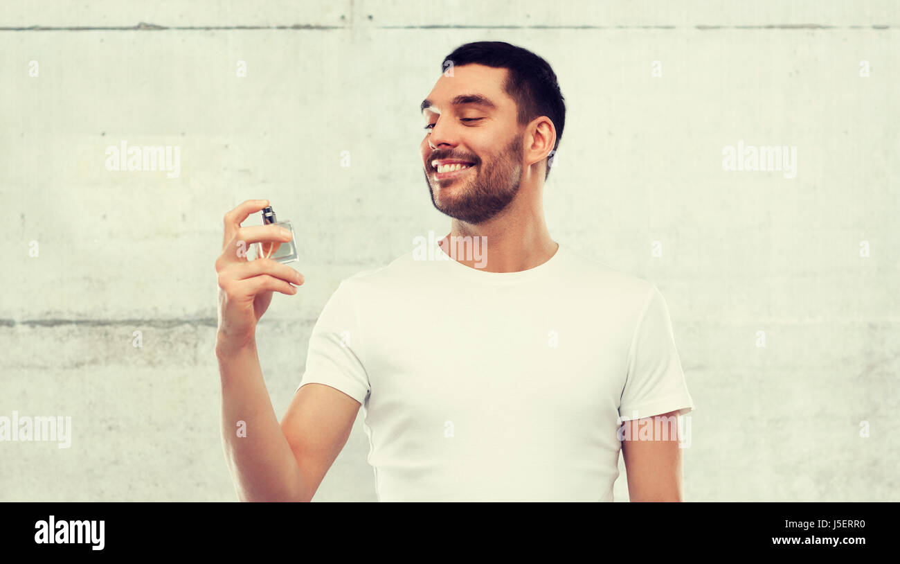 smiling man with male perfume over gray background - Stock Image