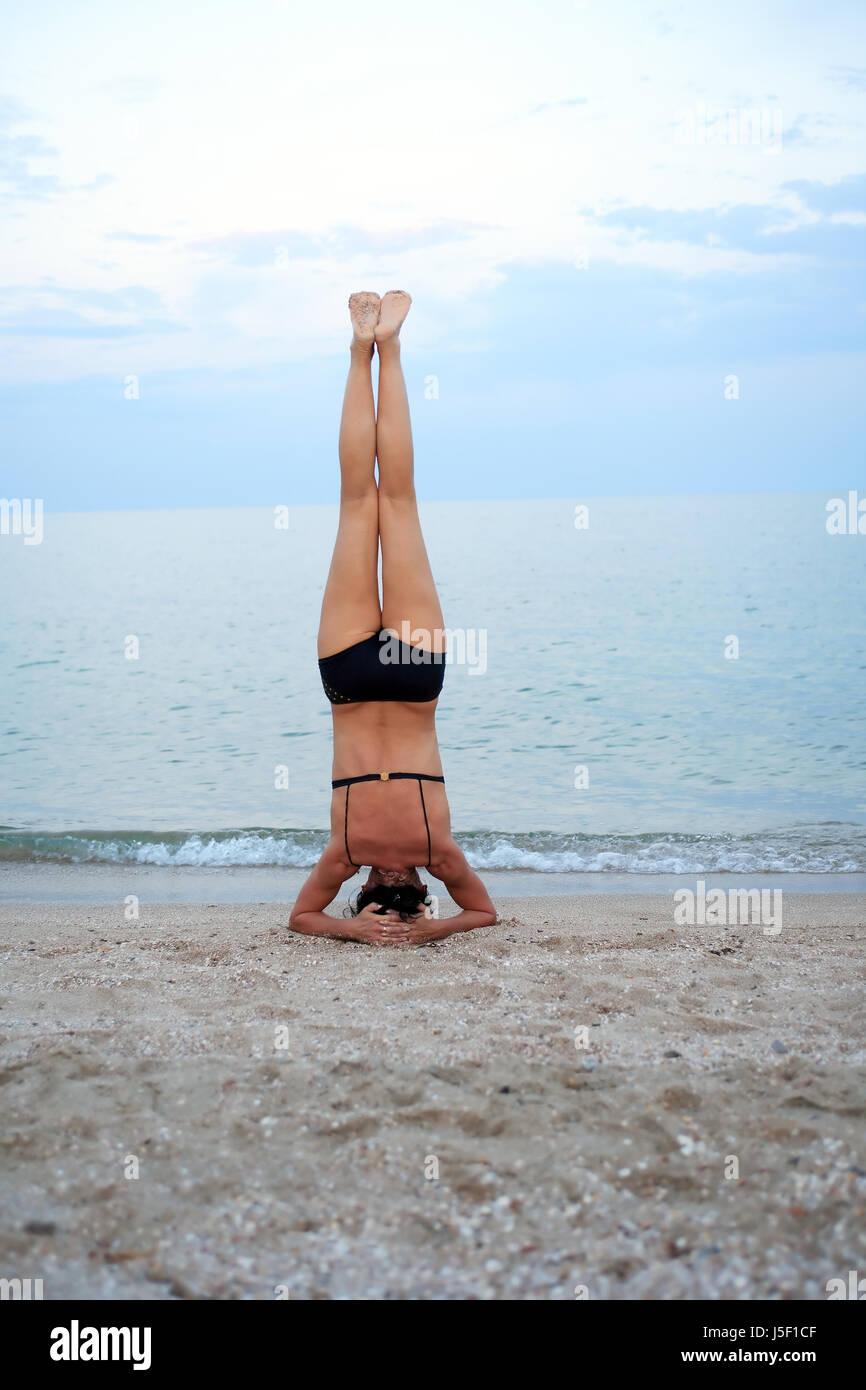 Svelte mature woman standing on her head near sea Stock Photo