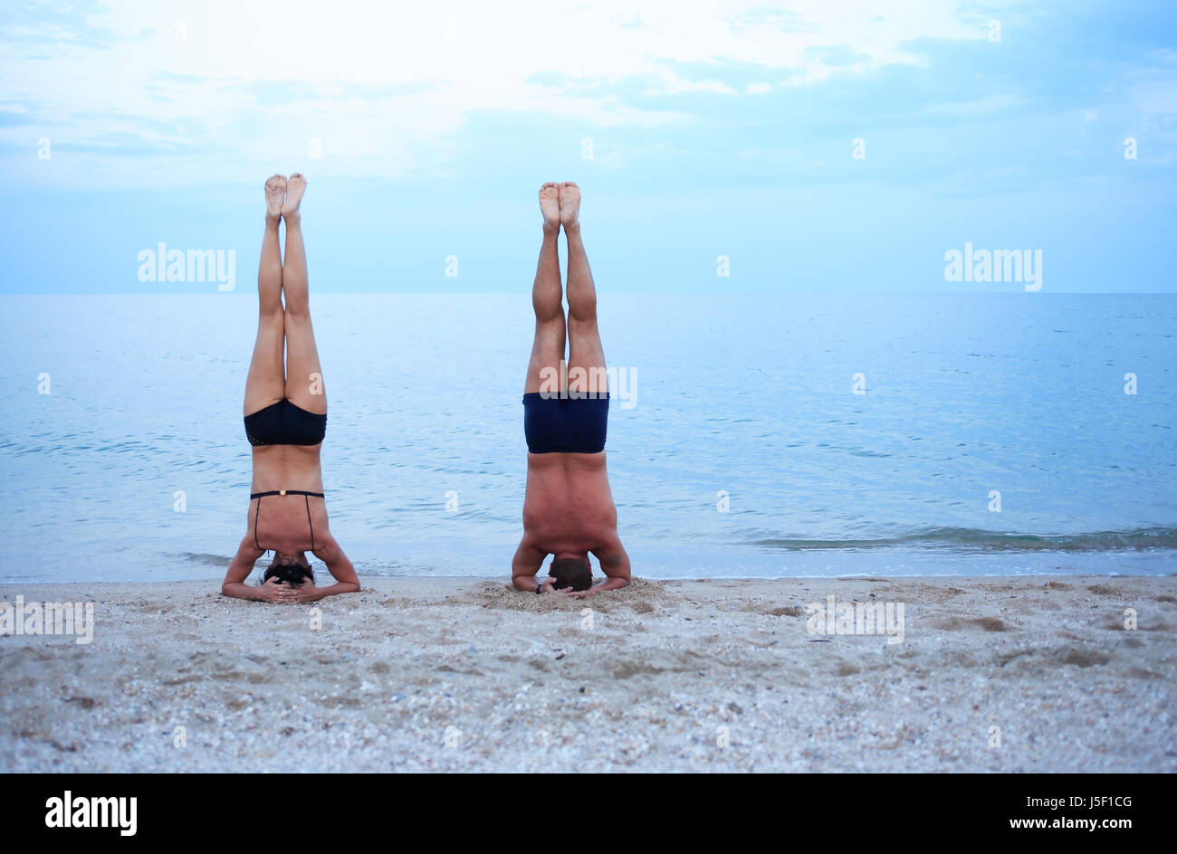 Svelte mature woman and strong man standing on head near sea - Stock Image