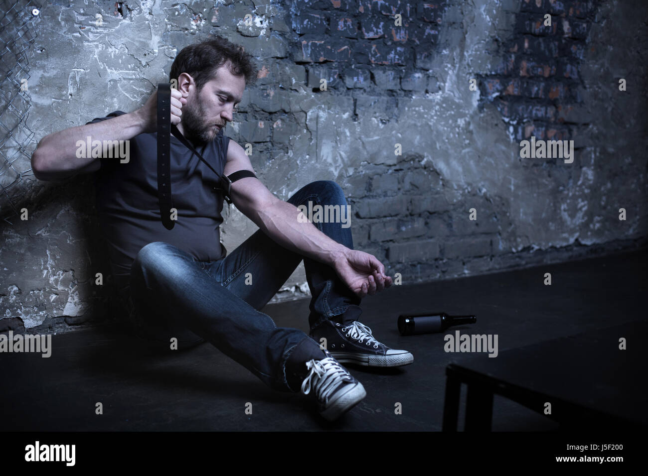 Lonely dope user applying rubber band in the darkness - Stock Image