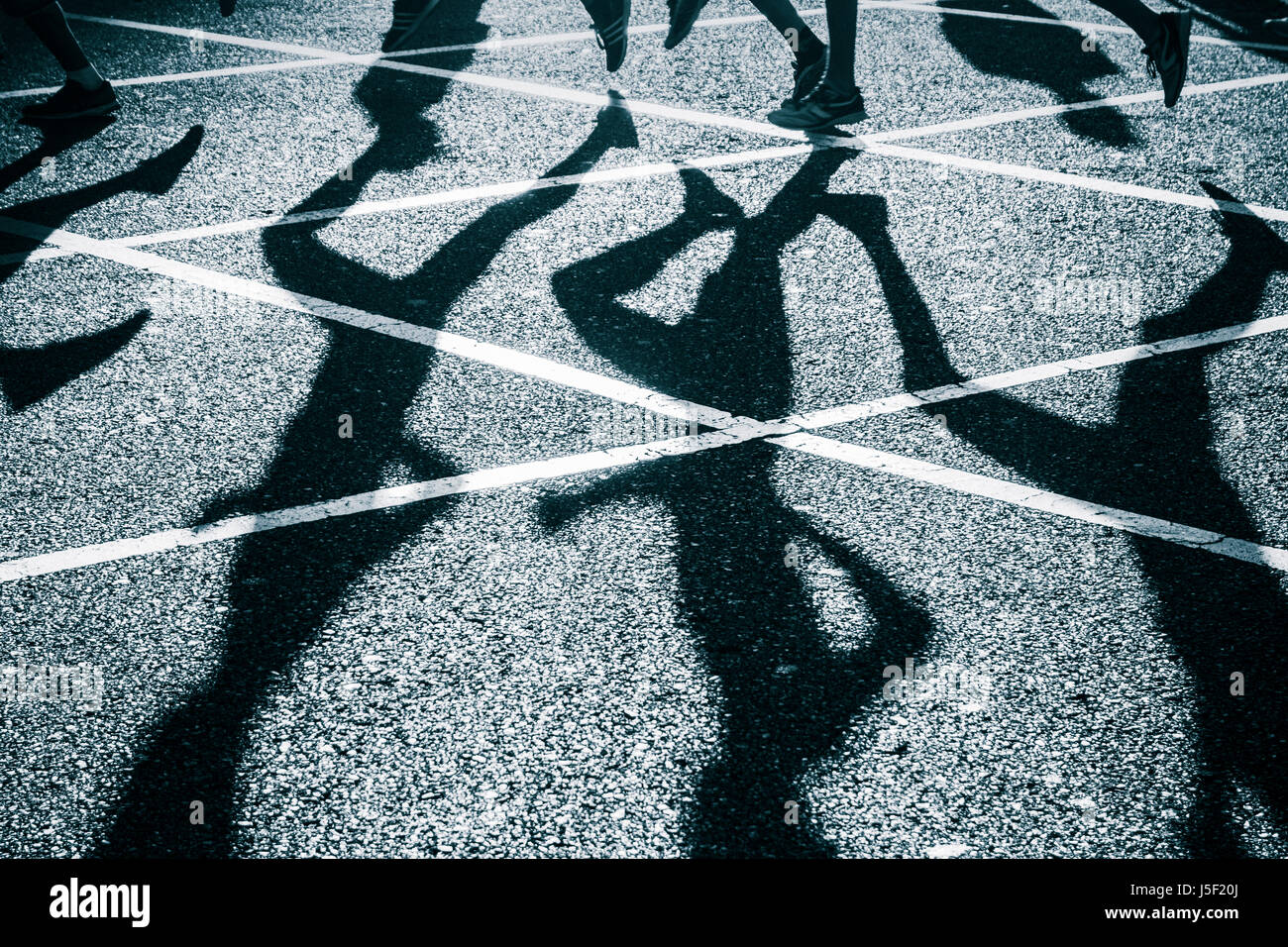 Runners shadows on road during city road race. - Stock Image