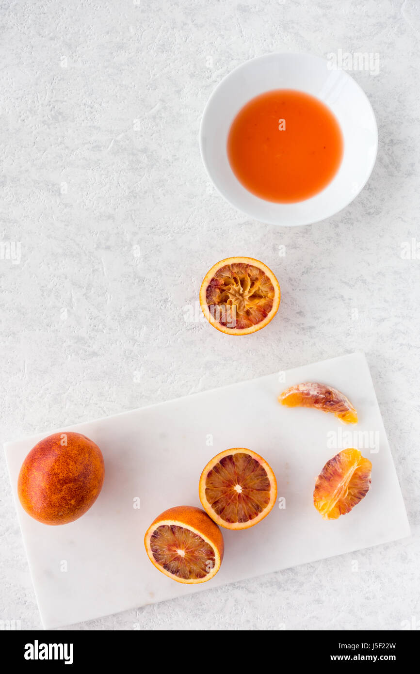 Whole, halved and squeezed blood oranges and fresh juice on white marble chopping board and white textured marbled - Stock Image