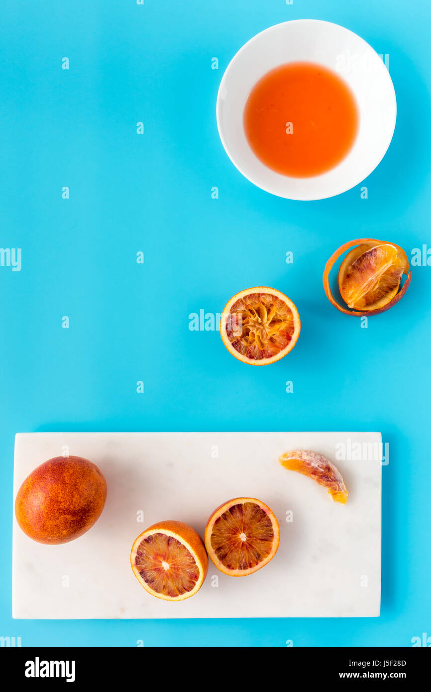 Whole, halved and squeezed blood oranges and fresh juice on white marble chopping board and solid blue background. Stock Photo