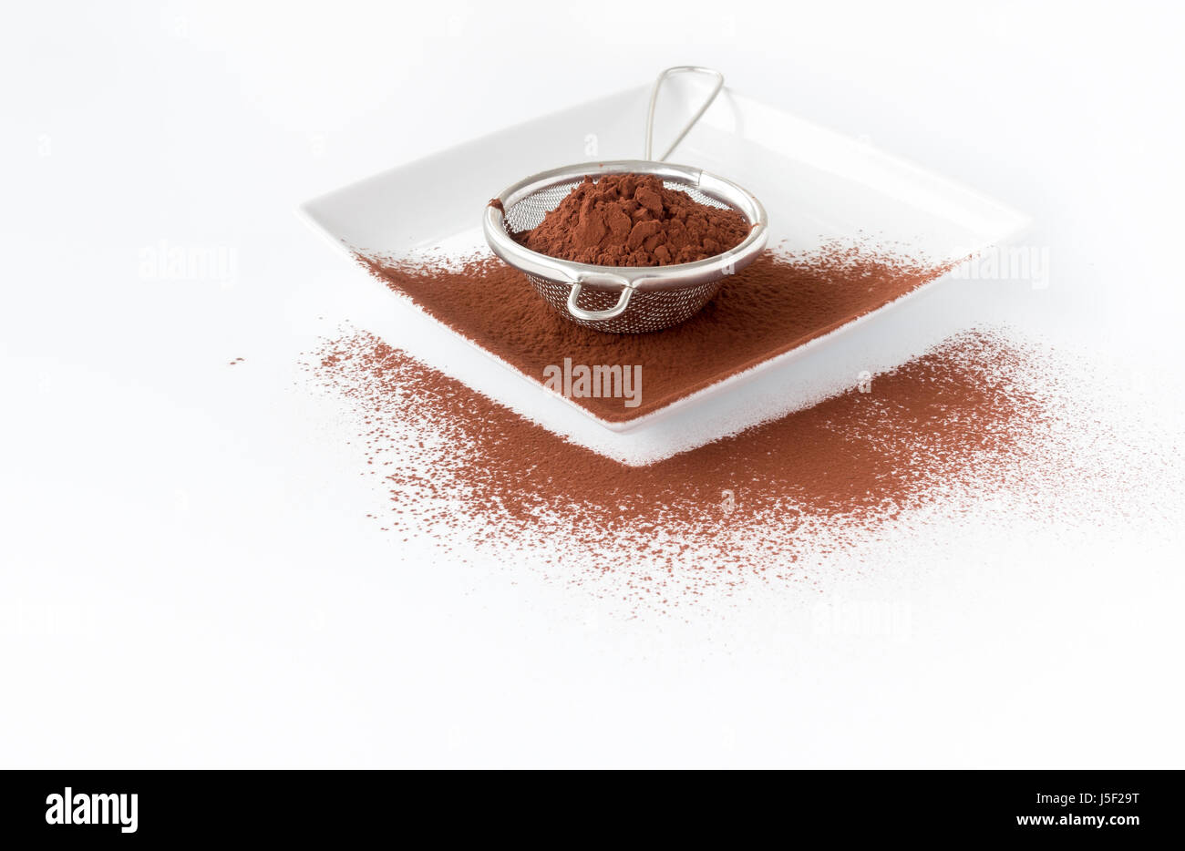 Close up of a metal sieve filled with cocoa powder on a white square porcelain plate. White background with copy - Stock Image