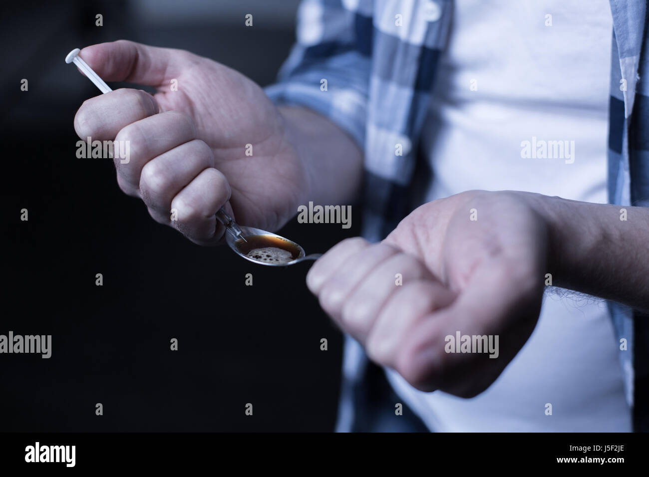 Criminal heroin addict preparing drug dose in the dark place - Stock Image