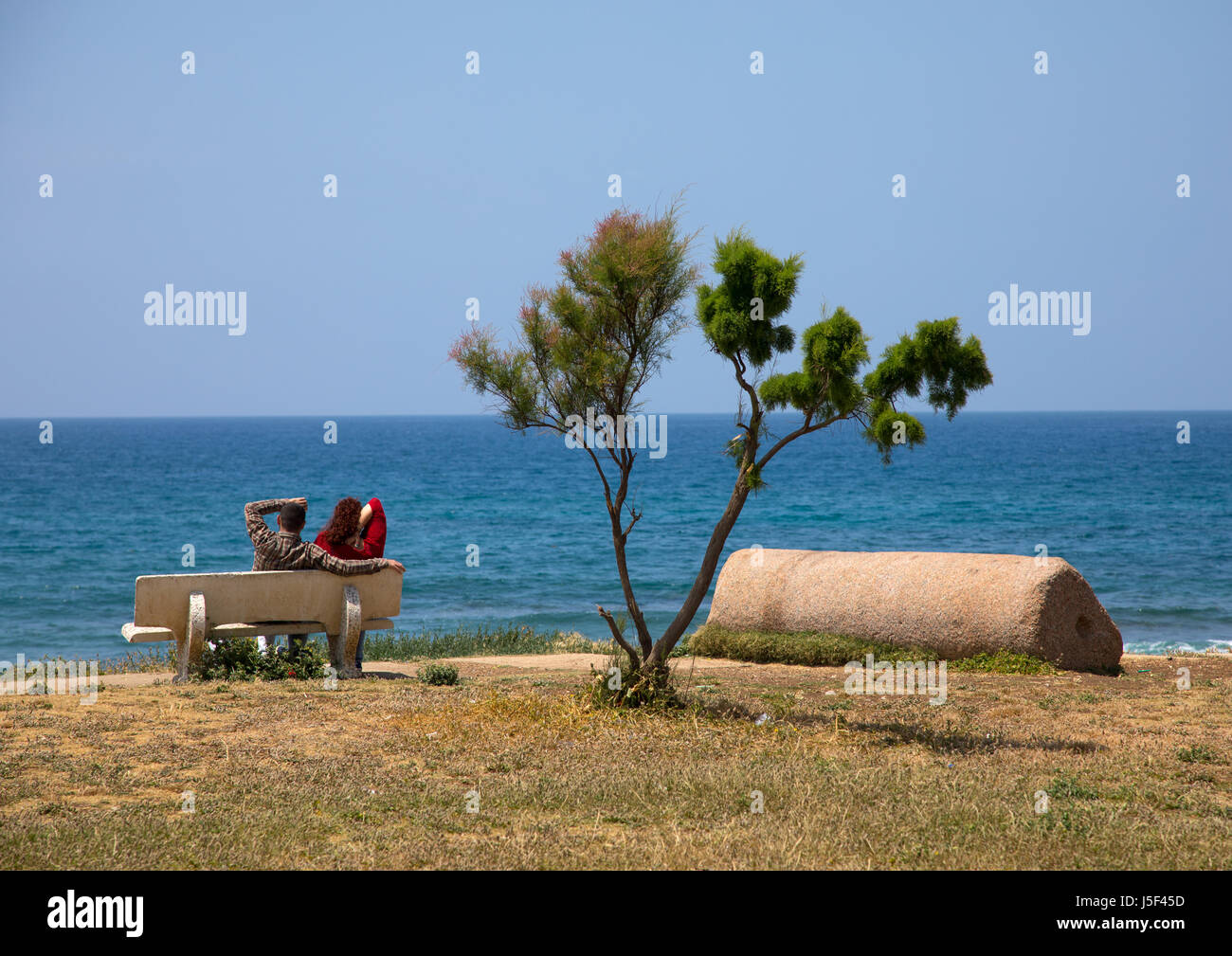 Couple sits on a bench in front of the sea, South Governorate, Tyre, Lebanon - Stock Image