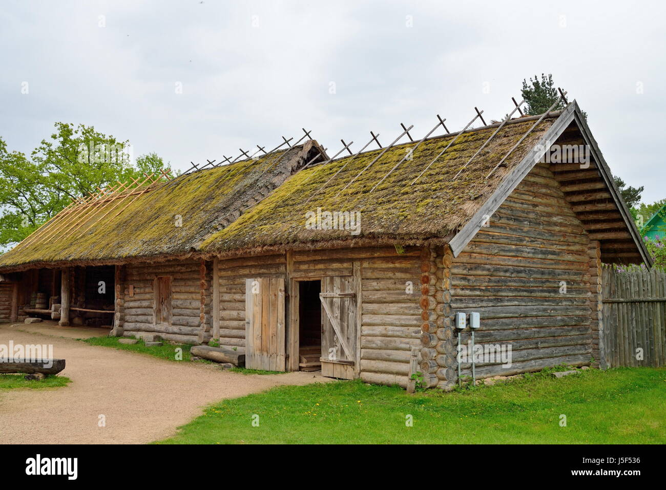Old Russian log hut in Pushkin Mikhailovskoe summer cloudy day - Stock Image