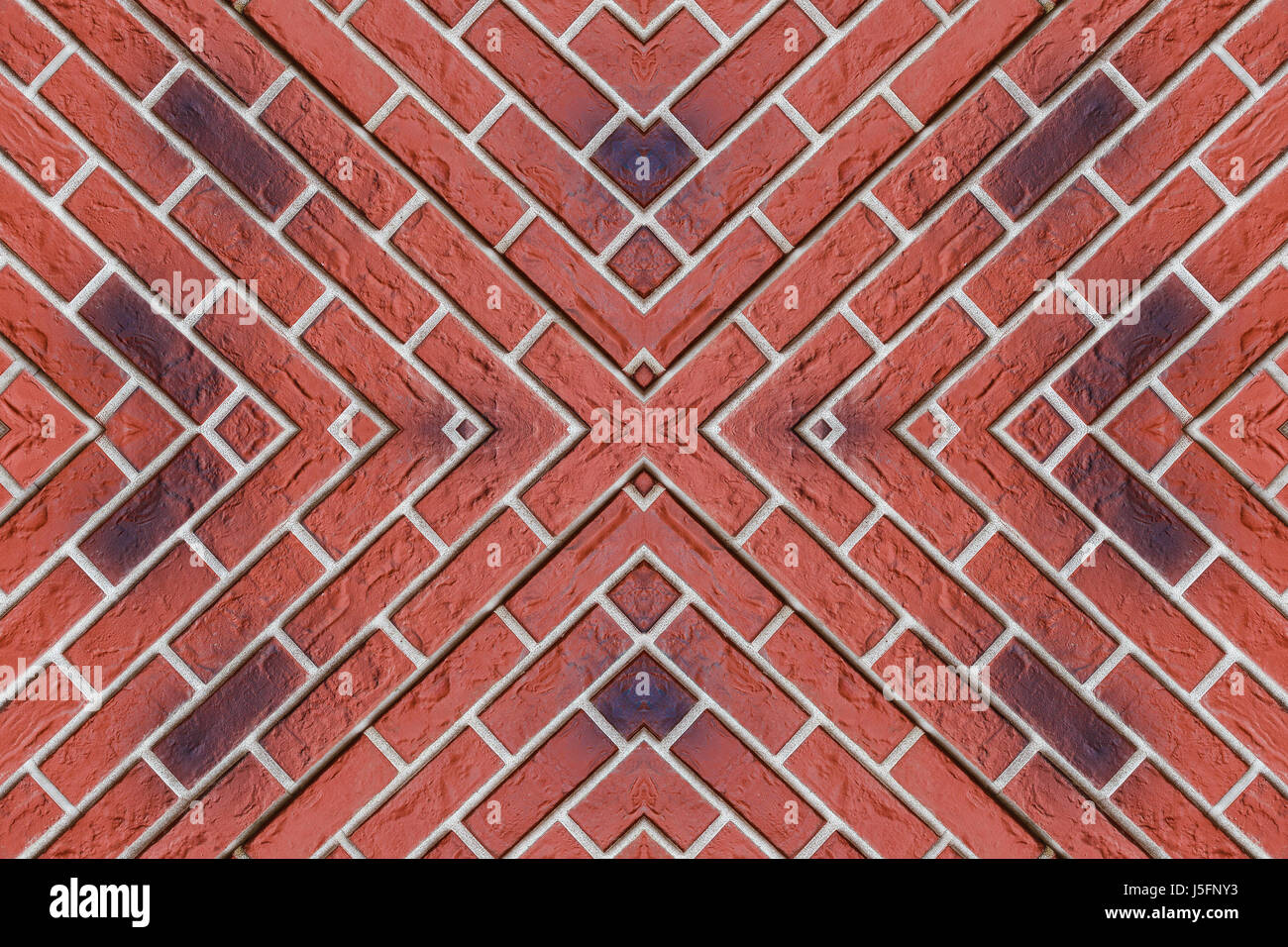 Wall of red brick. Bricks lined in the shape of a pattern and converge in the center - Stock Image