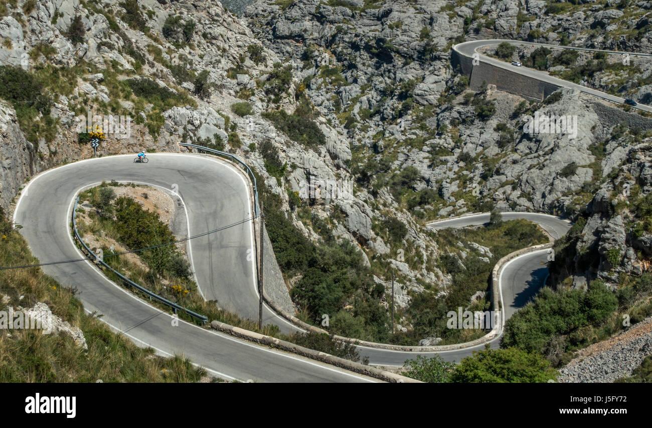 Female cyclist person on the famous winding road down to the coastal village of Sa Calobra, Mallorca, Majorca, Balearic - Stock Image