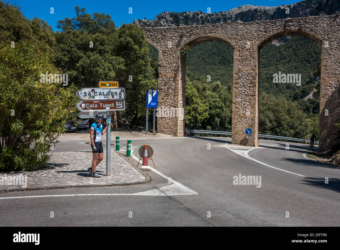 Female cyclist person underneath the signpost for the famous Sa Calobra hairpin road down to the coastal village, - Stock Image