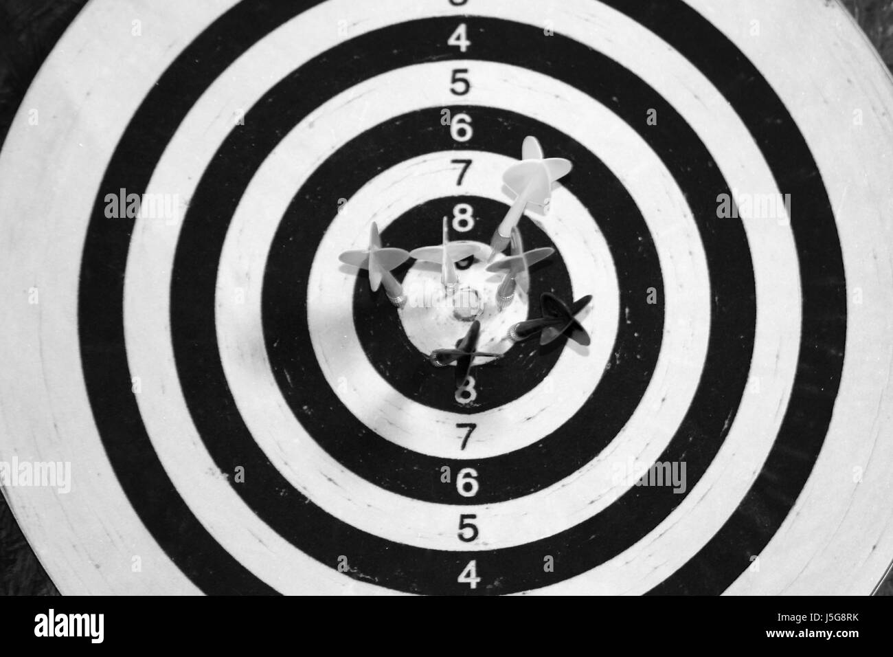 Black and white dart board with darts in the center. - Stock Image