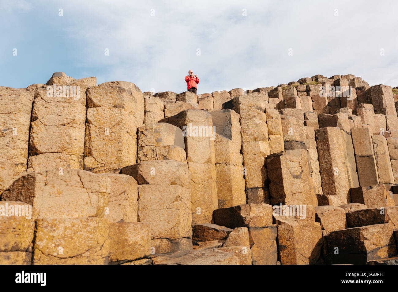 Male Tourist wearing a red jacket at The Giant's Causeway. - Stock Image