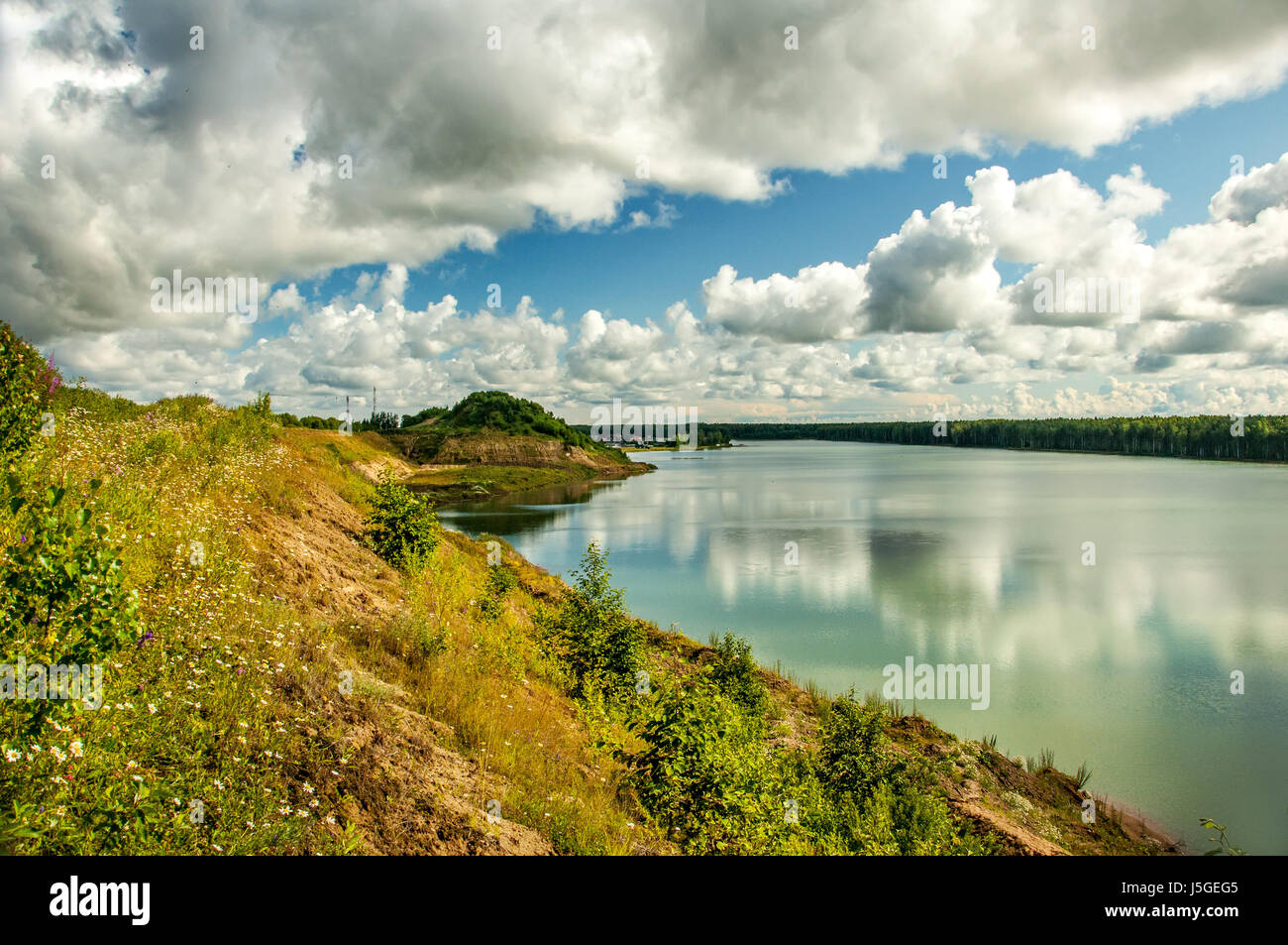Summer cloudy day on the shore of the quarry. - Stock Image