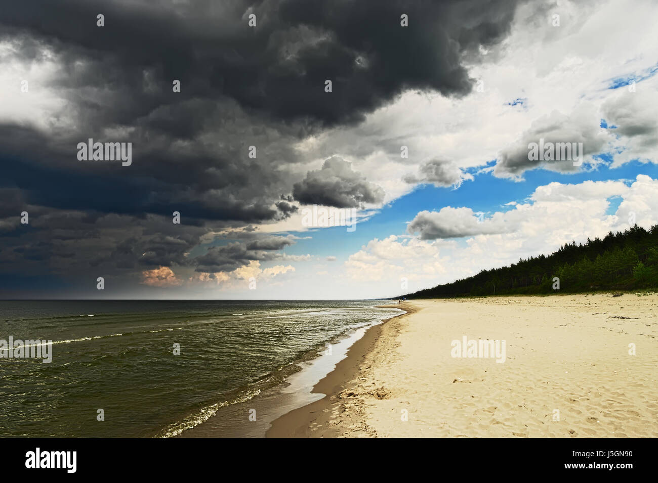 Seascape with dark, dramatic, stormy cumulonimbus cloud formation over the beach at Baltic sea. Stegna, Pomerania, - Stock Image