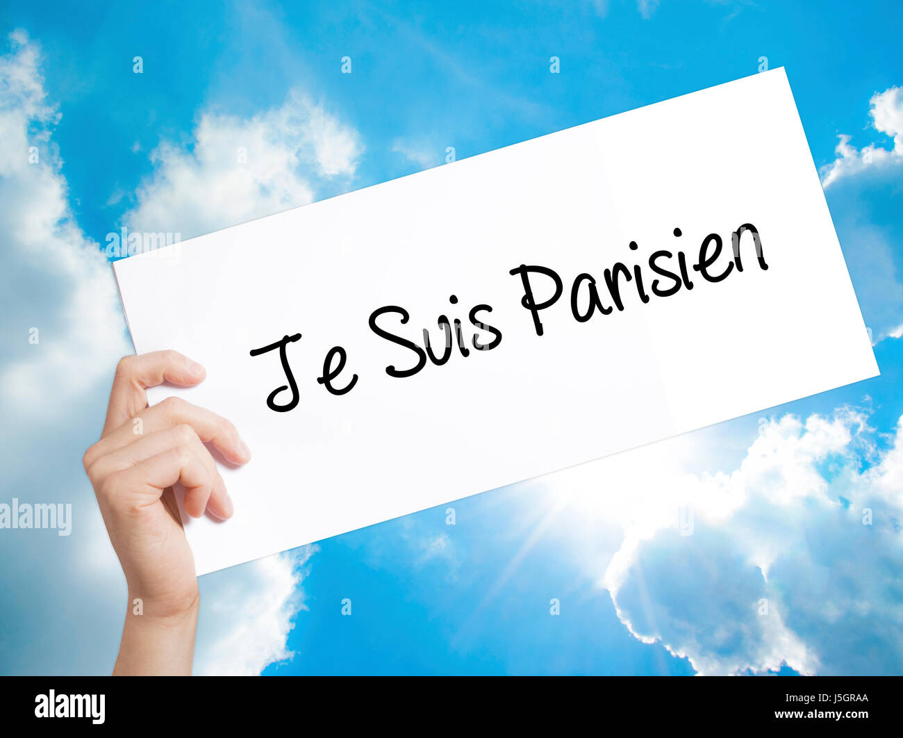 Je Suis Parisien Sign on white paper. Man Hand Holding Paper with text. Isolated on sky background. Stock Photo Stock Photo