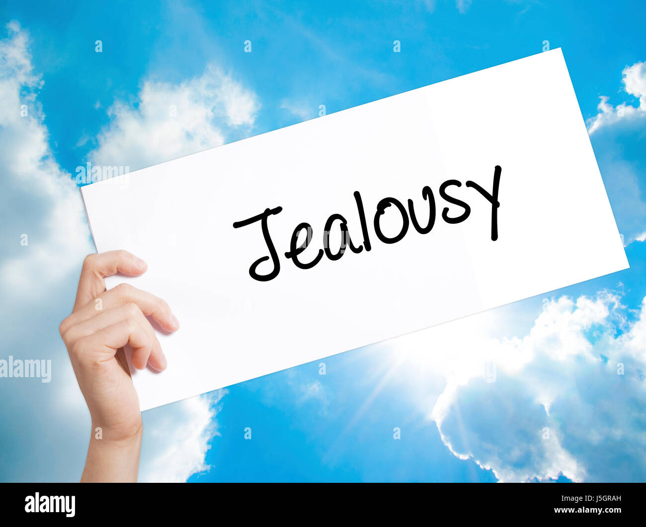 Jealousy Sign on white paper. Man Hand Holding Paper with text. Isolated on sky background.   Business concept. - Stock Image