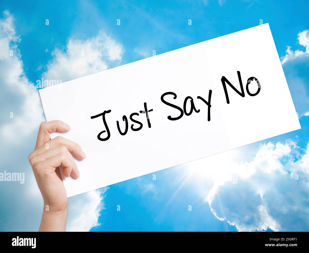Just Say No Sign on white paper. Man Hand Holding Paper with text. Isolated on sky background.   Business concept. - Stock Image