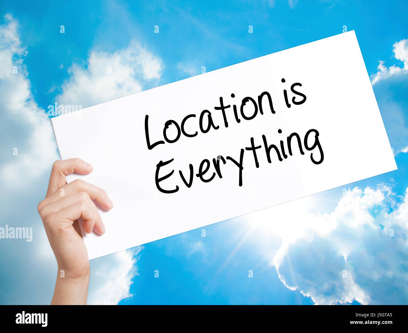Location is Everything Sign on white paper. Man Hand Holding Paper with text. Isolated on sky background.  Business - Stock Image