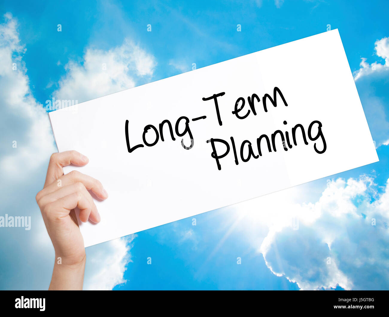 Long-Term Planning Sign on white paper. Man Hand Holding Paper with text. Isolated on sky background.  Business - Stock Image